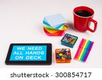 Small photo of Business Term / Business Phrase on Tablet PC - Colorful Rainbow Colors, Cup, Notepad, Pens, Paper Clips, White surface - White Word(s) on a cyan background - We Need All Hands On Deck