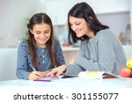 Small photo of Mom helping her daughter do her homework
