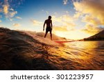Surfing at sunset. young man...