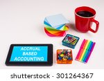 Small photo of Business Term / Business Phrase on Tablet PC - Colorful Rainbow Colors, Cup, Notepad, Pens, Paper Clips, White surface - White Word(s) on a cyan background - Accrual Based Accounting