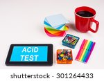 Small photo of Business Term / Business Phrase on Tablet PC - Colorful Rainbow Colors, Cup, Notepad, Pens, Paper Clips, White surface - White Word(s) on a cyan background - Acid Test