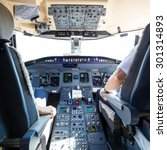 Small photo of Rear view of pilot and copilot flying comercial airplane. Interior of airplane cockpit. Instrument panels in pilot's cabin.
