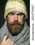 Small photo of Portrait of unsocial unshaven tramp man with long beard and hendlebar moustache in knitted yellow hat and grey scarf looking forward arching brow standing on black background, vertical picture