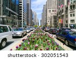 Small photo of CHICAGO, USA - MAY 24, 2014: The Magnificent Mile with lots of tulips planted in the median and cars passing by.