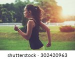 Stock photo pretty sporty woman jogging at park in sunrise light 302420963