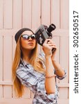 Small photo of Outdoor portrait of stylish photographer girl holding vintage retro camera,wearing bright trendy sunglasses and jacket,amazing view of city from the roof.Toned,lifestyle,accessorize,hiker