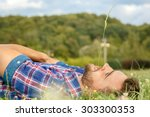 handsome man lying on the grass ... | Shutterstock . vector #303300353