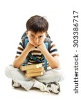 Small photo of Schoolboy bored, frustrated and overwhelmed by studying homework. Little boy sitting down on floor isolated on white background.