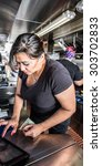Small photo of Female cashier with money on busy food truck