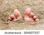Toes Buried In The Sand Of The...