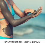 Woman Smearing Mud Mask On The...