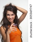 Small photo of Lovely brunette is holding flacon of parfume on the white background. Happy quean in orange shirt is smiling.