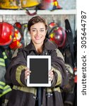 Small photo of Portrait of happy firewoman showing digital tablet at fire station