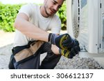 Small photo of handsome young man electrician installing air conditioning in a client house