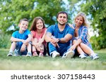happy family sitting on lawn | Shutterstock . vector #307158443
