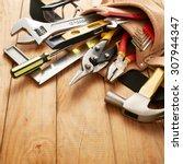 tools in tool belt on wood... | Shutterstock . vector #307944347