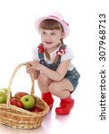 Small photo of Cute little girl with short bangs and long thin braids which are plaited with red ribbons, sat around a wicker basket in which lay a large fresh apples. Girl wearing pink hat , short denim overalls