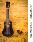 Small photo of Still life with old ukulele on wooden background