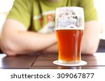 Small photo of Man in pub sitting behind glass of tasty craft beer