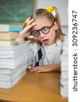Small photo of Overwhelmed pupil between stack of books on her desk in a classroom