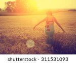 woman walking on wheat field in ... | Shutterstock . vector #311531093
