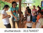 Small photo of Kanchanaburi, Thailand - July 21, 2013: Poor children line up to get donated stuffs from volunteers.