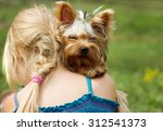 Stock photo yorkshire terrier on the shoulder of year old girl looking into the camera 312541373
