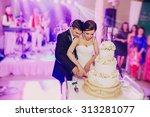 groom cutting the cake at their ... | Shutterstock . vector #313281077