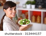 young woman eating fresh salad... | Shutterstock . vector #313444157