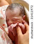 newborn baby in mother's arms two minutes after birth - stock photo