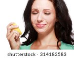 Small photo of Beautiful close-up portrait of young woman tasting lemon. Sour taste.
