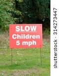 Small photo of Slow down to 5 miles per hour sign - children present