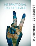 Small photo of a man hand patterned with an Earth map (furnished by NASA) giving the V sign, as symbol of peace, and the sentence international day of peace