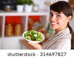 young woman eating fresh salad... | Shutterstock . vector #314697827