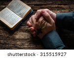 Man Praying Before A Bible...