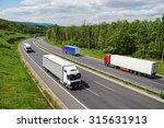 Trucks Traveling On An Asphalt...