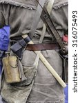 Small photo of WHEATON, ILLINOIS/USA - SEPTEMBER 12, 2015: A tomahawk hangs by a flask on the back of a militiaman in period garb at a reenactment of the American Revolutionary War (1775-1783).