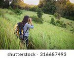 Tourist looking through binoculars considers wild birds in the Khao yai national park Thailand