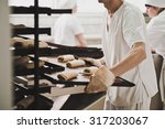 A Worker Carries A Tray Of...