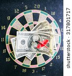 Small photo of dart Darts accurately hit the target in one hundred dollar bills as a sign of business success