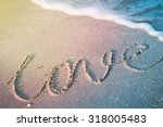 the word love on beach with wave | Shutterstock . vector #318005483