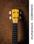 Small photo of still life of yellow ukulele with brown leather background