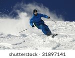 Skier moving down on ski slope against blue sky. - stock photo