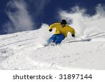 Freeride skier in powder snow against blue sky. - stock photo
