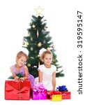 Small photo of Two happy, joyful little girls in big white bows on her head ,dressed in festive dresses, surrounded by many gifts . The girls sat around the Christmas tree and consider a gift from my parents
