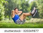 young athlete doing sit ups in... | Shutterstock . vector #320269877