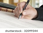 man signing papers, books and home office in background - stock photo