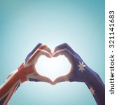 Small photo of Australia national flag on people hands in heart shape isolated on sky background for labour day and national Anzac holiday celebration