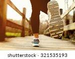 young woman jogging across a... | Shutterstock . vector #321535193