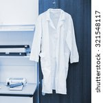 Small photo of white robe hanging on a door in laboratory, blue toning